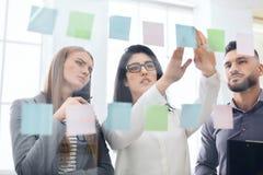 Employés collant des rappels sur le conseil de visualisation dans le bureau image stock