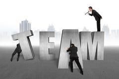 Employés commandants d'homme d'affaires pour déplacer le mot d'ÉQUIPE ainsi que Image stock