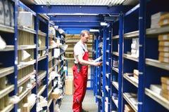 Employés d'atelier de réparations de voiture dans l'entrepôt pour des pièces de rechange pour r photographie stock libre de droits