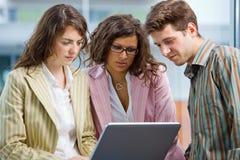 Employés de bureau à l'aide de l'ordinateur portatif Photographie stock libre de droits