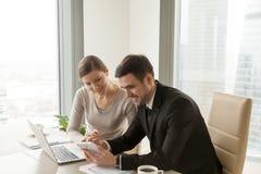 Employés de bureau à l'aide du comprimé numérique et de l'ordinateur portable, secteur d'affaires de la téléphonie mobile Photos stock
