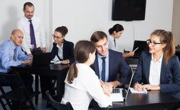 Employés de bureau avec des ordinateurs portables ayant un jour productif au travail photo stock