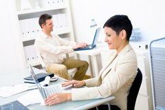 Employés de bureau avec des ordinateurs portatifs Photo stock