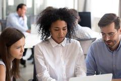 Employés de bureau avec le chef féminin d'Afro-américain à l'aide de l'ordinateur portable image stock