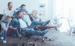 Employés de bureau ayant l'amusement avec une chaise pivotante Image stock