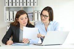 Employés de bureau coworking comparant des documents photo stock