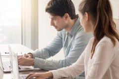 Employés de bureau de sexe masculin et féminins à l'aide de deux ordinateurs portables sur le lieu de travail images stock
