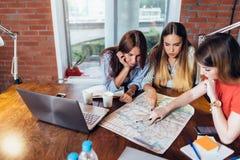 Employés de bureau féminins prévoyant des vacances utilisant la carte Photographie stock