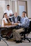 Employés de bureau heureux se réunissant à la table dans la salle de réunion photos stock