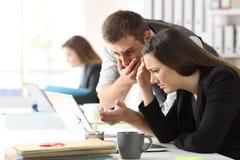 Employés de bureau inquiétés vérifiant le contenu en ligne image stock