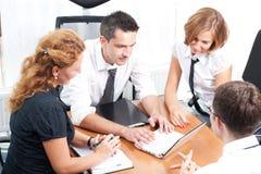 Employés de bureau réels posant pour l'appareil-photo Photographie stock libre de droits