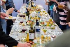 Employés de la société au banquet Tableau avec les délicatesses, l'alcool et les casse-croûte Une réception de gala images stock