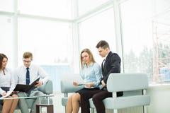 Employés de la société avec des documents se reposant dans la salle de réception avant la conférence Image stock