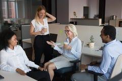 Employ?s divers ayant la conversation agr?able pendant la pause-caf? photos stock