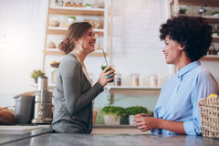 Employés féminins se tenant derrière le compteur de jus Image stock