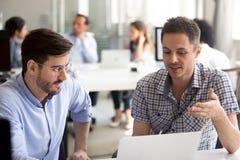 Employés masculins travaillant ensemble sur le projet en ligne, utilisant l'ordinateur portable images stock