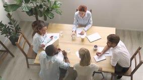 Employés millénaires et entraîneur s'asseyant dans la vue de salle de réunion d'en haut clips vidéos