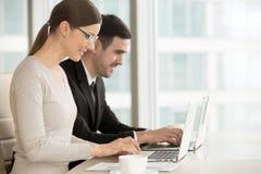 Employés ou chefs de file des affaires de sourire utilisant l'ordinateur portable Photographie stock libre de droits