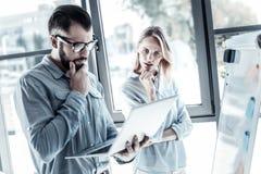 Employés réfléchis sérieux employant l'ordinateur portable et la pensée Image libre de droits