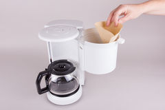 Employ coffee filter in coffee maker. A woman employ the filter in the coffee machine with hand royalty free stock photo