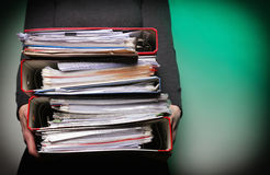 Employé de bureau féminin portant une pile de dossiers Images libres de droits