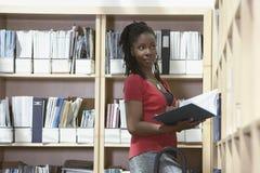 Employé de bureau sur l'échelle dans la chambre de stockage de fichier Photographie stock libre de droits