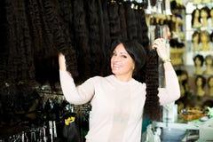 Employé de magasin féminin vendant les queues de cheval naturelles de grêle Photographie stock libre de droits