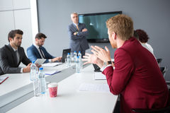 Employ present his opinions to director and collogues. Male employ present his opinions to director and collogues in meeting room royalty free stock photo