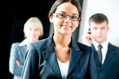 Employee. Portrait of beautiful employee with glasses on the background of businesspeople Stock Photos