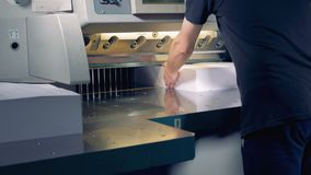An employee is adjusting two large piles of paper under a cutter which ploughs them in four parts. 4K stock footage