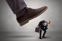 Employee afraid of the big boss foot. Employee is afraid of the big boss foot, which is stepping down him Stock Images