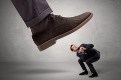 Employee afraid of the big boss foot Royalty Free Stock Photo