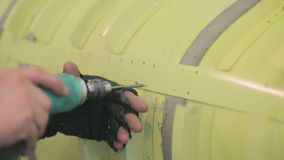 Employee aircraft manufacturing plant drills holes in fuselage of aircraft. stock video footage