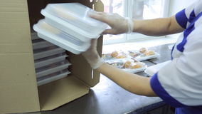 An employee of airline catering facility puts trays of food in a box. Cardboard box is used for temporary storage and transportation of food. All foods hot and stock video footage
