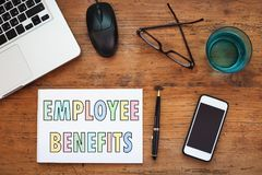 Employee benefits. Concept, note in the notepad on wooden table royalty free stock images