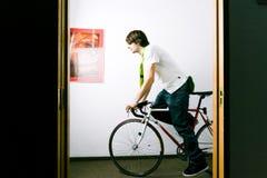 Employee on bike. Young businessman or employee on bicycle, on a corridor Stock Photo