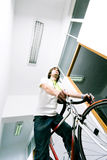 Employee on bike. Young businessman or employee on bicycle, on a corridor Stock Photography