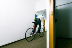Employee on bike. Young businessman or employee on bicycle, on a corridor Royalty Free Stock Photography