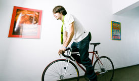 Employee on bike. Young businessman or employee on bicycle, on a corridor Royalty Free Stock Photos