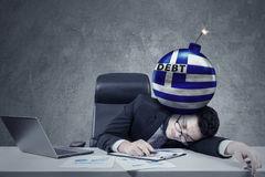 Employee with bomb of debt and Greek flag Stock Photos