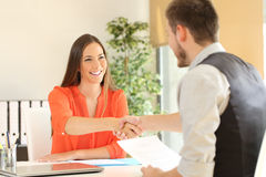 Employee and boss handshaking after a job interview. Happy employee and boss handshaking after a successful job interview at office Stock Photography
