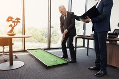 The employee came to the director with a report. Director plays golf in the office Stock Photo