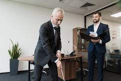 The employee came to the director with a report. Director plays golf in the office Stock Image