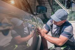 An employee of a car service examines a car paintwork royalty free stock images
