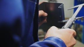 Employee checks metal detail with measuring tool in workshop