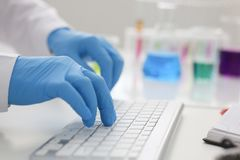 Employee chemical laboratory teacher. Chemist knocks his fingers keyboard makes notes electronic journal records the analysis data from reactions examining test Royalty Free Stock Photography