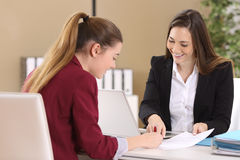 Employee or client signing a contract. Employee or client and interviewer signing a contract on a desktop in an office interior Royalty Free Stock Image
