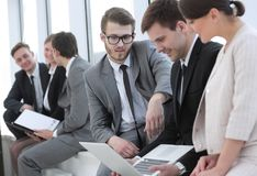 Employee with colleagues before the briefing. Employee of a company with colleagues to discuss working papers royalty free stock image
