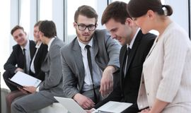 Employee with colleagues before the briefing. Employee of a company with colleagues to discuss working papers royalty free stock photo