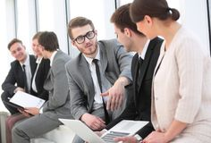 Employee with colleagues before the briefing. Employee of a company with colleagues to discuss working papers stock image